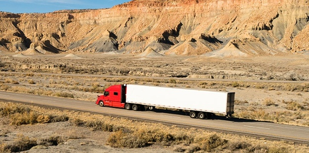 semi truck driving down an empty road