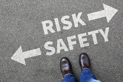 man standing over a risk vs safety sign