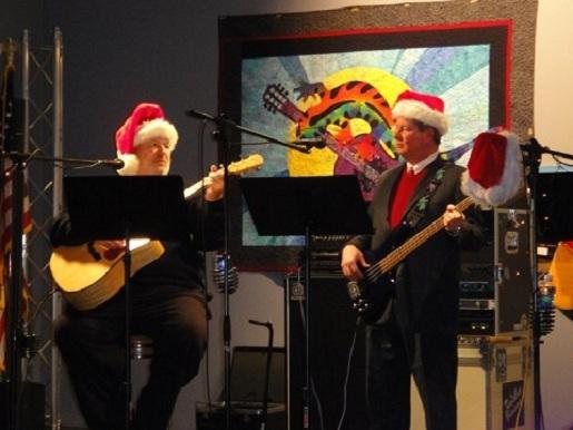 Mark Gardner (right) performs holiday favorites at Santafest.