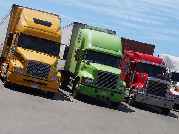 Yellow, green and red semi-trailer trucks